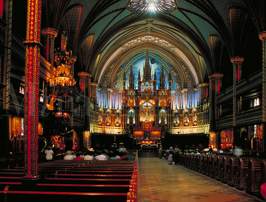 The impressive altar and pews of the Notre Dame Basilica in Montreal are visible while beautifully illuminated by dim, colorful light. Montreal, Canada Quebec.