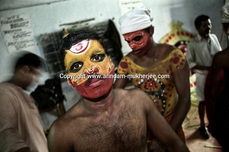 A Thayam artist is being prepared before his performance, Thirupunithura, Ernakulam, Kerala, India
