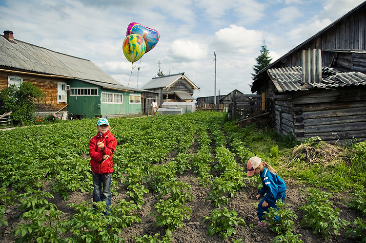Children are plaing in a potato field in a small village of Kenozero. For some time many people live on subsistence farming only and depend from a fair yield to live winter monthes