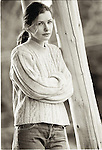 Portrait of healthy, attractive young white woman leaning against wooden post