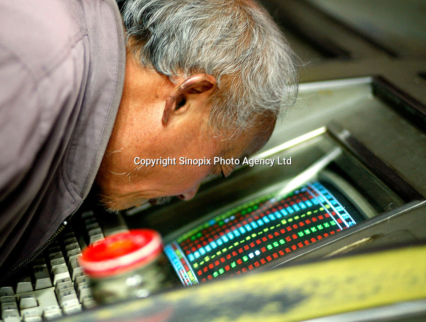 An elderly man squints into the screen of a trading computer at a local securities exchange house in Shanghai, China. Chinese Exchange lost 3,000 points, almost nine percent of its value yesterday. China has a wild roller-coaster stock market but this is one of the largest single day drops..28 Feb 2007