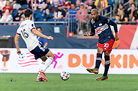 FOXBOROUGH, MA - AUGUST 18: Teal Bunbury #10 of New England Revolution passes the ball as Steven Birnbaum #15 of D.C. United closes during a game between D.C. United and New England Revolution at Gillette Stadium on August 18, 2021 in Foxborough, Massachusetts.