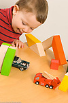 Two year old toddler boy playing with toy vehicles and tunnel made from blocks, sticking tongue out in excitement