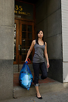 Montreal (Qc) CANADA, July 24, 2007 - Model Released photo- A young asian woman carrries a recycling blue bag outside , on Notre-Dame street in Old-Montreal,a fter the city decide to swith from bins to bags for its curbside recycling collect.<br /> <br /> photo : (c) images Distribution