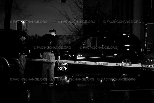 Chicago Illinois USA<br /> April 2009<br /> <br /> Chicago police officers investigate for shell casings after a young man was murdered in his car. On Chicago's South side is shooting appeared to be gang related.