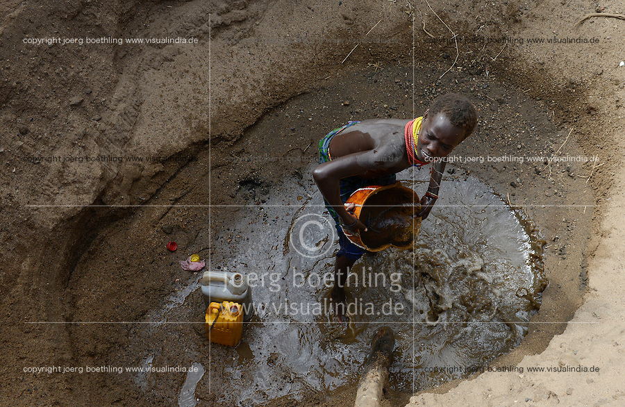 ETHIOPIA, Southern Nations, Lower Omo valley, Kangaten, village Kakuta, Nyangatom tribe, shepherds give water to their goats from water holes at dry river Kibish, girl Akiru / AETHIOPIEN, Omo Tal, Kangaten, Dorf Kakuta, Nyangatom Hirtenvolk, Hirten traenken das Vieh aus Wasserloechern am trocknen Fluss Kibish, Maedchen Akiru, 12 Jahre