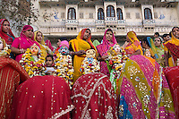 Rajasthani women bow down to Shiva and his wife Parvati at the GANGUR FESTIVAL in UDAIPUR, RAJASTHAN, INDIA