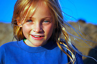 Girl on beach with warm light, sand sprinkles on face and messy hair.