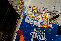 "Champeta music party posters, created by Runner's collective, are seen on the wall in Cartagena, Colombia, 7 December 2018. Hidden in the dark, narrow alleys of Bazurto market, a group of dozen young men gathered around José Corredor (""Runner""), the master painter, produce every day hundreds of hand-painted posters. Although the vast majority of the production is designed for a cheap visual promotion of popular Champeta music parties, held every weekend around the city, Runner and his apprentices also create other graphic design artworks, based on brush lettering technique. Using simple brushes and bright paints, the artisanal workshop keeps the traditional sign painting art alive."