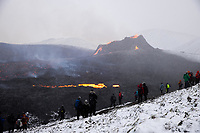 People watching the eruption in Geldingadalir, Iceland. A volcanic eruption in the Reykjanes peninsula, near Reykjavik, started on 19 march 2021. The eruption in the area of Geldingadalir is considered small but some geologists are predicting it might be active for months or years to come. It takes around 90 minutes to to hike to the eruption from the road and since erupting people have been sightseeing.