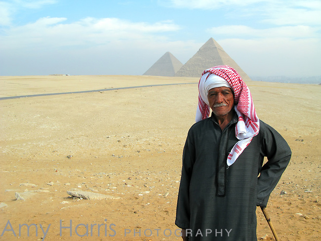 Egyptian man in traditional dress with the Great Pyramids in the distance in Cairo, Egypt.