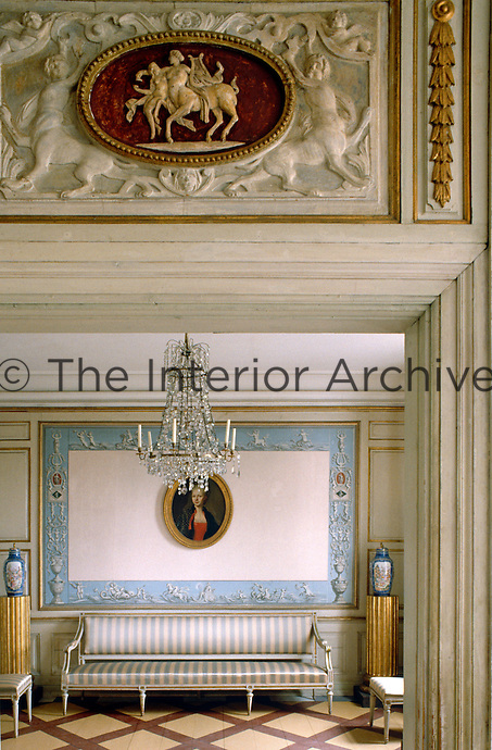 A carved relief hangs above the doorway leading to a small sitting room furnished with a crystal chandleier and a dainty canape