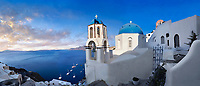 Panoramic of the traditional Greek Orthodox churches of Oia (ia), Cyclades Island of  Thira, Santorini, Greece.<br /> <br /> The settlement of Oia had been mentioned in various travel reports before the beginning of Venetian rule, when Marco Sanudo founded the Duchy of Naxos in 1207 and feudal rule was instituted on Santorini. n 1537, Hayreddin Barbarossa conquered the Aegean islands and placed them under Sultan Selim II. However, Santorini remained under the Crispo family until 1566, passing then to Joseph Nasi and after his death in 1579 to the Ottoman Empire.