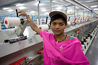 INDIA Madhya Pradesh, Maral Overseas Ltd. textile factory process fairtrade cotton, spinning unit produce yarn from raw cotton, worker at spinning machine / INDIEN Madhya Pradesh , Verarbeitung von fairtrade Baumwolle bei Maral Overseas Ltd., Arbeiterin an Spinnmaschine