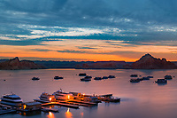 Colorful twilight on Lake Powell and typical Page marina houseboats lit up under a dramatic, cloudy sky, at the Arizona and Utah border, USA