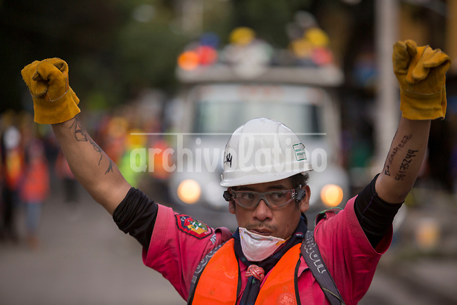 Rescue workers rise their fist asking for silence to identify noises from possible survivor of a collapsed building in the South of Mexico DF city.