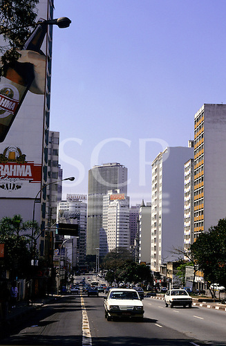 Sao Paulo, Brazil. City street running between high-rise buildings; Brahma beer advertisement on the side of a building.