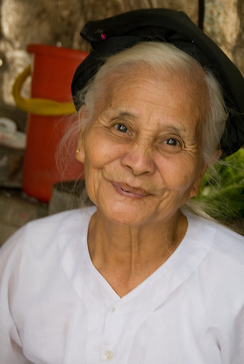 An older woman in the small village of Tho Ha just outside of Hanoi, Vietnam exudes warmth and happiness with her smile.