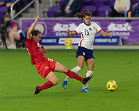 ORLANDO CITY, FL - FEBRUARY 18: Alex Morgan #13 has the ball poked away by a sliding Vanessa Gilles #23 during a game between Canada and USWNT at Exploria stadium on February 18, 2021 in Orlando City, Florida.