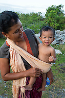 Bali, Indonesia.  Balinese Mother Carrying her Little Boy in a Shoulder Sling.
