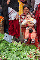 Kathmandu, Nepal.  Micro-credit Loan Recipient Poses in the Market with her Son.   Her Loan from the Non-Profit NGO CORE, Creating Opportunities and Resources for the Excluded, allows her to sell lettuce and other vegetables in the local market.  Both wear a tikka, or a bindi, a red mark between their eyebrows, a decorative mark of Hinduism traditionally said to protect against demons or bad luck.