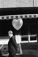 Switzerland. Canton Zürich. Zuerich. An old man walks on the sidewalk and passed by an inflated heart. © 1989 Didier Ruef
