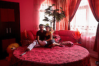 Rafael Ion, 16, sits with his fiance, Maria, 15, in his room in his grandfather's mansion. Buzescu is known for it's ultra-wealthy Roma and their bizarre mansions that line the main street. The Roma of Buzescu are part of the Kalderash clan and are known for being coppersmiths and dealing with metal scraps. After the fall of the communist regime in the late 80's, they stripped old factories of their metals and some made a small fortune re-selling them. They are also known for making cazane, copper stills that produce alcohol such as palinka, a plum brandy.