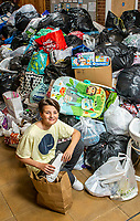 BNPS.co.uk (01202 558833)<br /> Pic: MaxWillcock/BNPS<br /> <br /> Pictured: Volunteer William Webb, 14, sorting the pile of donations.<br /> <br /> Parental consent given.<br /> <br /> A flood of donations for Afghan refugees has inundated a church which has been left with a 24ft long stack of parcels.<br /> <br /> Ross Donaldson posted on a Facebook community group asking if anyone had clothes to offer, sparking an overwhelming response from his community.<br /> <br /> After organising to keep donations at Immanuel Church, Bournemouth, Dorset, he arrived the next morning to find a pile of bags.