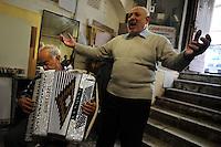 Vecchi amici. Old friends..Nello storico quartiere di San Lorenzo a Roma, un gruppo di amici si riunisce per pranzo,nella falegnameria di Graziano Azzurri.L' occasione è il compleanno di Vincenzo, 76 anni ex tassista..In the historic district of  San Lorenzo in Rome, a group of friends meets for lunch, in carpentry of Graziano Azzurri. On the occasion of the birthday of  Vincenzo, 76 years ex taxi driver..Mariano, decoratore,suona la fisarmonica. Mariano play the accordion.Gino canta,Gino sing....