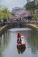 Japan, Okayama Prefecture, Kurashiki. Bride and groom in a wedding boat on the river.