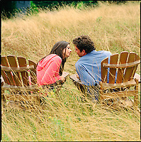 Couple sitting on Adirondack chairs in tall grass<br />