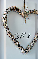 One of a pair of woven raffia hearts that hangs on the entrance hall cupboard