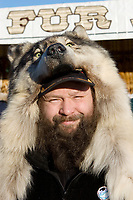 A man in a wolf fur cap at the Fur Rondy Festival, down town Anchorage