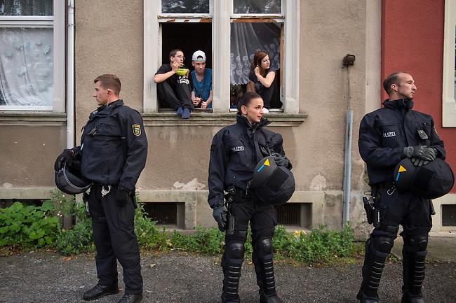 Wilkommensfest fuer Fluechtlinge im saechsichen Heidenau.<br /> Nachdem Polizei und politisch Verantwortliche vergeblich versucht hatten ein Wilkommensfest fuer Fluechtlinge mit dem Argument des Polizeilichen Notstands zu verbieten feierten hunderte Menschen zusammen. Fuer die Fluechtlinge waren Kleidungs- und Sachspenden nach Heidenau gebracht worden, die in Berlin, Dresden und anderswo gesammelt wurden.<br /> Zahlreiche Polizeikraefte waren zum Schutz des Festes im Einsatz.<br /> Im Bild: Jugendliche Anwohner betrachten die Fluechtlingsunterstuetzer, die mit einer Demonstration zum Bahnhof ziehen um nach Hause zu fahren.<br /> 28.8.2015, Heidenau<br /> Copyright: Christian-Ditsch.de<br /> [Inhaltsveraendernde Manipulation des Fotos nur nach ausdruecklicher Genehmigung des Fotografen. Vereinbarungen ueber Abtretung von Persoenlichkeitsrechten/Model Release der abgebildeten Person/Personen liegen nicht vor. NO MODEL RELEASE! Nur fuer Redaktionelle Zwecke. Don't publish without copyright Christian-Ditsch.de, Veroeffentlichung nur mit Fotografennennung, sowie gegen Honorar, MwSt. und Beleg. Konto: I N G - D i B a, IBAN DE58500105175400192269, BIC INGDDEFFXXX, Kontakt: post@christian-ditsch.de<br /> Bei der Bearbeitung der Dateiinformationen darf die Urheberkennzeichnung in den EXIF- und  IPTC-Daten nicht entfernt werden, diese sind in digitalen Medien nach §95c UrhG rechtlich geschuetzt. Der Urhebervermerk wird gemaess §13 UrhG verlangt.]