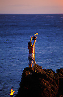 A man performs a sunset ceremony off Black Rock at the north end of Kaanapali Beach.