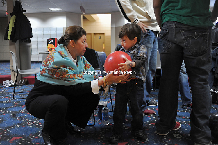 Marie Sherzai, 55, of Fairfax, Virginia, an Afghan immigrant to the U.S., assists her grandson, Omid Gish, 4, after he lifted a heavy bowling ball by himself during the Afghan Bowling Tournament in Annandale, Virginia on February 28, 2010.