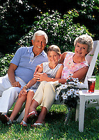 Portrait of smiling grandparents and granddaughter sitting outside.