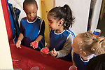 Education Preschool 2 year olds group of boy and two girls talking and playing with play dough