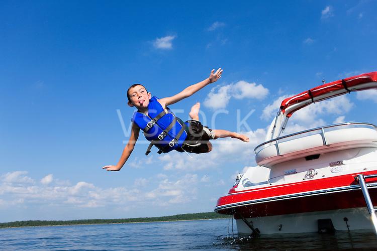 USA, Missouri, Stockton, Stockton Lake, boy (6-7) jumping off boat