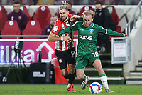 Barry Bannan of Sheffield Wednesday tries to shake off a challenge from Brentford's Emiliano Marcondes during Brentford vs Sheffield Wednesday, Sky Bet EFL Championship Football at the Brentford Community Stadium on 24th February 2021