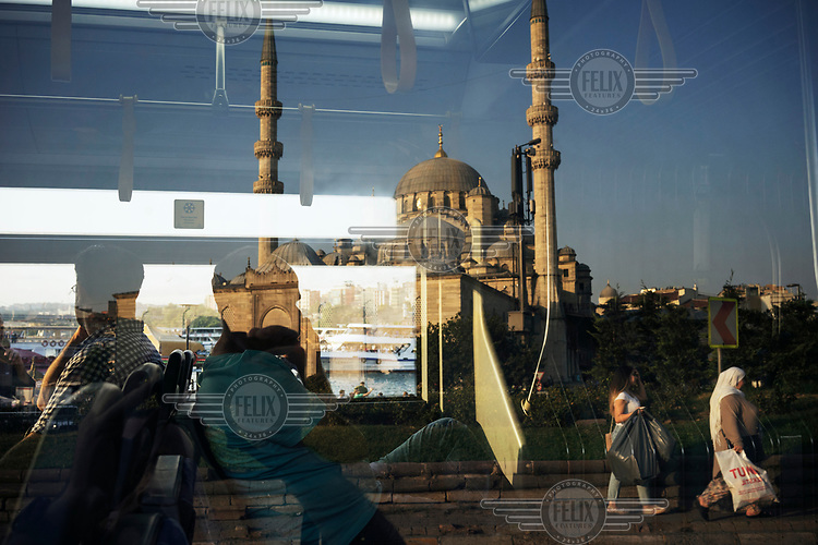 Men sitting on a bus are reflected in its windows  while in the background is the Yeni Cami mosque.