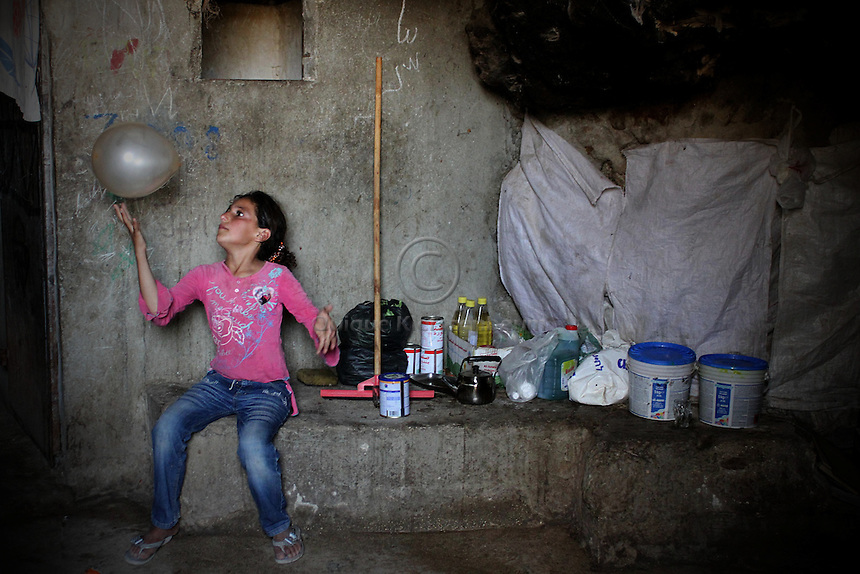 """A Palestinian girl plays with a baloon in the cave she  lives in Jenba a Palestinian town of 50 families seats in an area called by the IDF as """"Firing Zone 918"""" and is located in the southern Hebron hills near the town of Yatta.  Spread over 30,000 dunams, it includes twelve Palestinian villages.  According to OCHA figures, 1,622 people lived in the area in 2010, and according to local residents the number of inhabitants currently stands at about 1,800. For over a decade, the residents of twelve uniquely traditional Palestinian villages in the area of Masafer-Yatta in the south Hebron hills have lived under the constant threat of demolition, evacuation, and dispossession.The State's insistence on evacuation of Firing Zone 918 in part or in whole, if acceptance by the HCJ, might result in an immediate humanitarian disaster for almost two thousand souls, the destruction of villages, and the eradication of a remarkable way of life that has endured for centuries."""