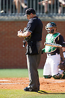 Home plate umpire Barry Chambers makes a note that the Canisius manager had been given a warning for arguing during the game against the Charlotte 49ers at Hayes Stadium on February 23, 2014 in Charlotte, North Carolina.  The Golden Griffins defeated the 49ers 10-1.  (Brian Westerholt/Four Seam Images)