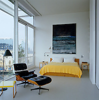 An Eames armchair and foot stool stand at one end of this light and spacious master bedroom
