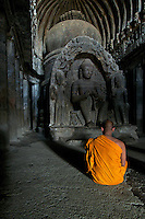 Buddhist Monk inside one of the Ellora Caves Aurangabad, India.The famous Ellora caves are located in the lap of the Chamadari hills. These historical caves are regarded as world heritage and are situated 18 miles northwest of Aurangabad.  .A wonderful example of cave temple architecture, the world heritage Ellora caves own elaborate facades and intricately carved interiors. These carved structures on the inner walls of the caves reflect the three faiths of Hinduism, Buddhism and Jainism. These exotic caves were carved during 350 AD to 700 AD period. .Ellora caves are hewn out of basaltic rock of the Deccan trap, and are datable from circa 5th century A.D. to 11th century A.D. In all 34 caves were excavated here out of which Cave 1 to 12 are Buddhist, 13 to 29 are Brahmanical and 30 to 34 are Jaina. Cave 10 in Ajanta Caves contains the oldest Indian paintings of historical period, made around the 1st century BC.<br />