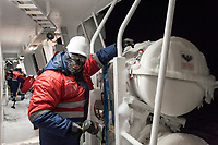 Members of deck crew clear ice from the exterior of the icebreaker and supply ship the 'Fedor Ushakov' as it makes its way through the Barents Sea along the Northern Sea Route.<br />