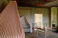 In the corner of the nursery stands a tiled stove and the bed and the cot are covered in brighly patterned red and white canopies