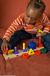 20 month old toddler baby girl playing with toy wooden shape sorter vertical