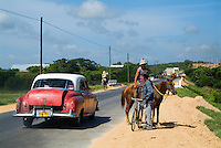Classic American car passing by a cowboy and a cyclist talking on a countryside road, Cuba.