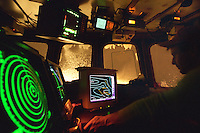 "Assistant skipper Jeff Morehouse guides the fishing vessel ""Polar Lady"" through a stormy night using GPS, radar, sideband radio, depth finders, and other electronic equipment in the wheelhouse during an opilio crab season in the Bering Sea in January 1995. Nights are long and cold in the arctic in the winter.  Crab fishing in the Bering Sea is considered to be one of the most dangerous jobs in the world.  This fishery is managed by the Alaska Department of Fish and Game and is a sustainable fishery.  The Discovery Channel produced a TV series called ""The Deadliest Catch"" which popularized this fishery. Today this fishery, largely based out of Dutch Harbor, AK has been consolidated resulting in a lot less boats fishing."